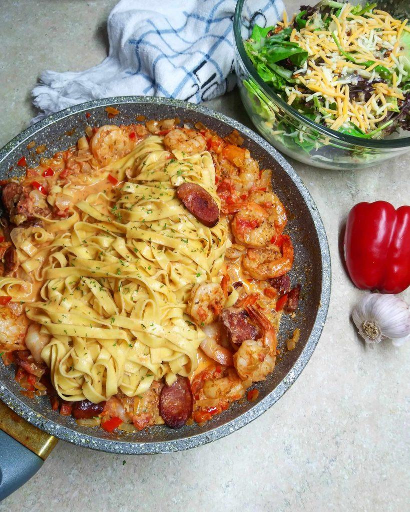 pan of cajun shrimp and sausage pasta with salad