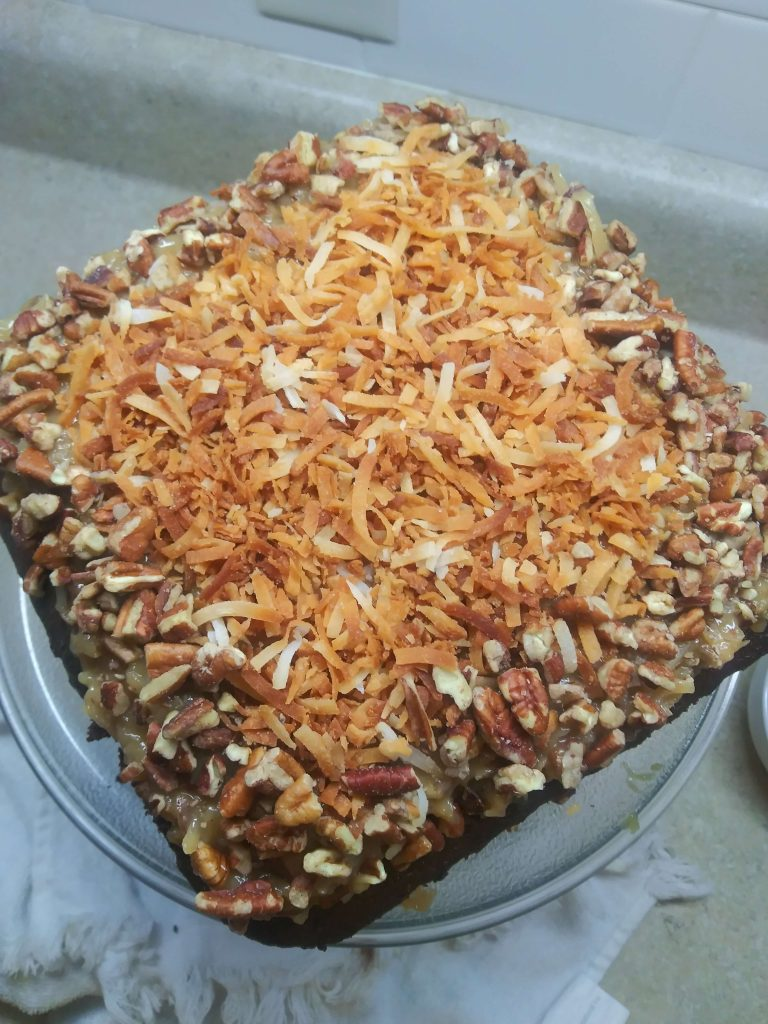 top view of square cake topped with toasted coconut and pecans