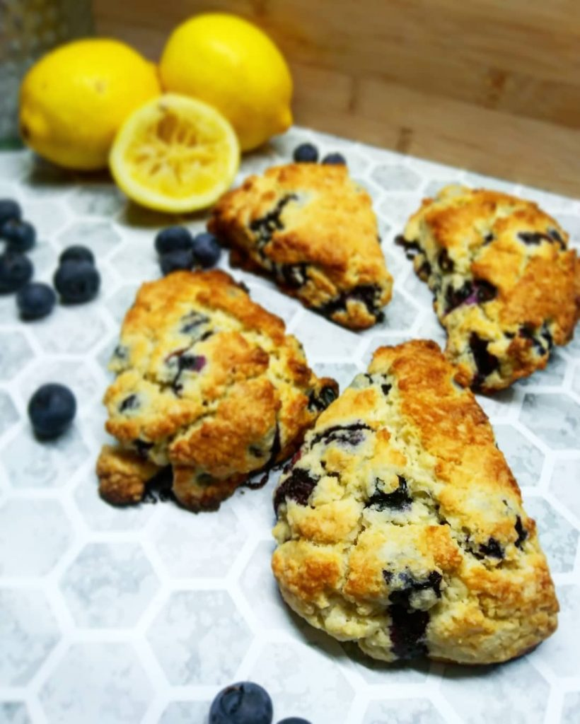 four lemon blueberry scones placed with fresh lemons and blueberries