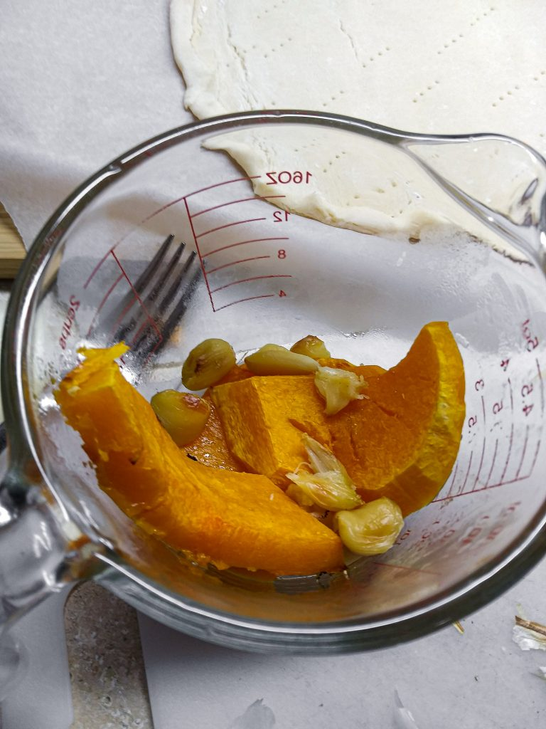 butternut squash and roasted garlic in measuring cup.