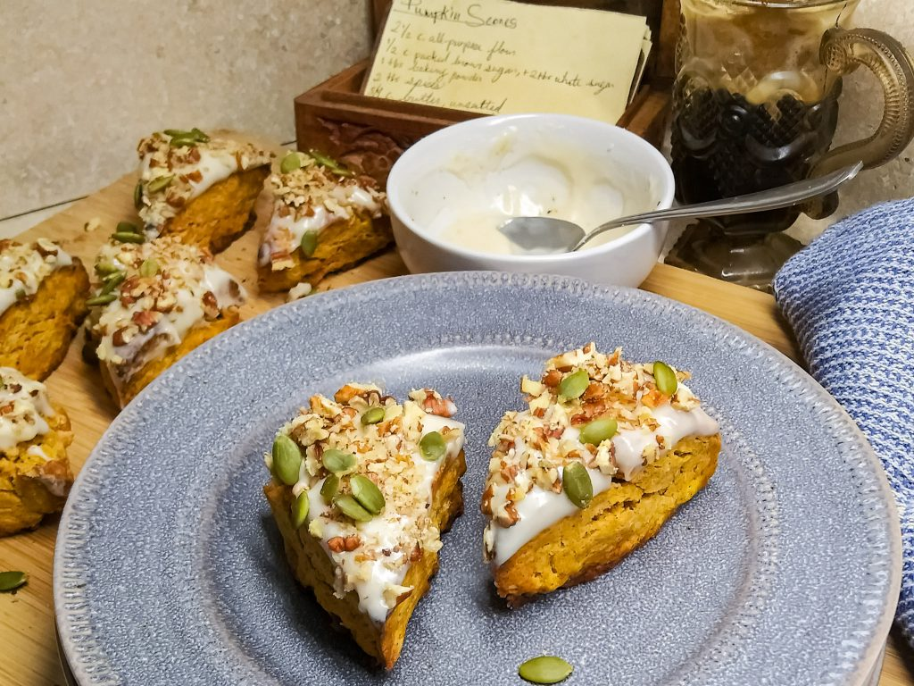 pumpkins scones topped with pepitas and nuts on a plate with recipe card.
