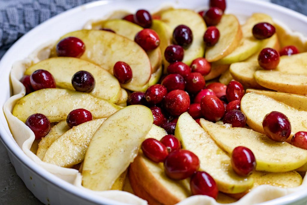 fresh sliced apples and cranberries in pie shell.