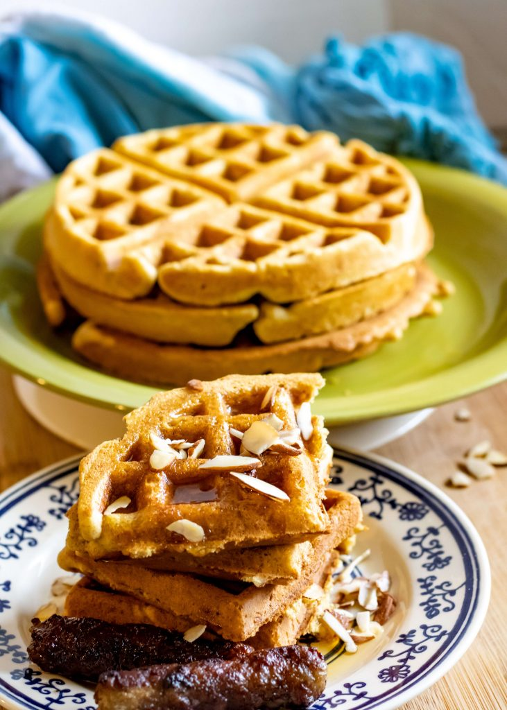 stack of waffles and a serving of belgian waffles topped with maple syrup and sliced almonds, served with 2 sausage links.