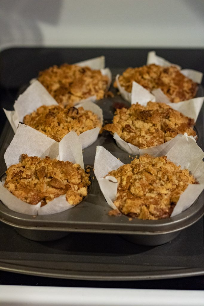 fresh out of the oven baked maple pecan banana bread muffins with crumb topping.